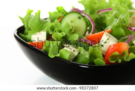 greek salad in black plate over white