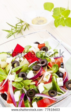Greek salad in bowl close up, olive oil dressing and fresh herbs in background.