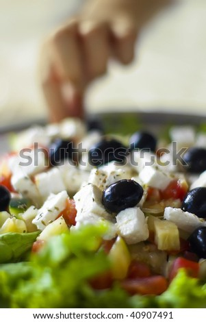 Greek salad in shallow depth of field with a hand in the background