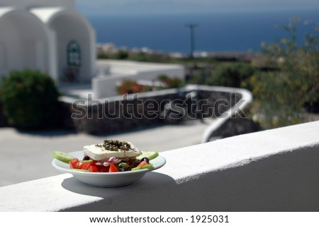 greek salad in sharp focus with cycladic architecture in background over aegean sea