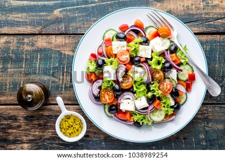 Greek salad of fresh cucumber, tomato, sweet pepper, lettuce, red onion, feta cheese and olives with olive oil. Healthy food, top view