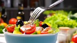 Greek salad on fork with feta cheese and olives, fresh vegetable salad served with healthy food ingredients, mediterranean cuisine