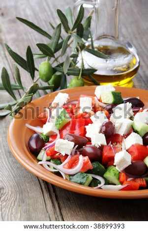Greek salad on the rustic plate and olive branch