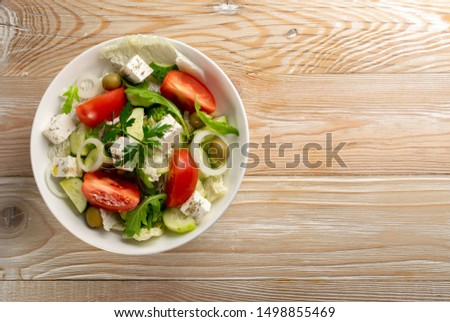 Greek salad or horiatiki with large pieces of tomatoes, cucumbers, feta cheese and olives in white bowl top view, copyspace. Village salad with diced mozzarella, arugula, parsley, spices and oil