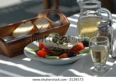 greek salad with country bread and home made white wine taverna setting