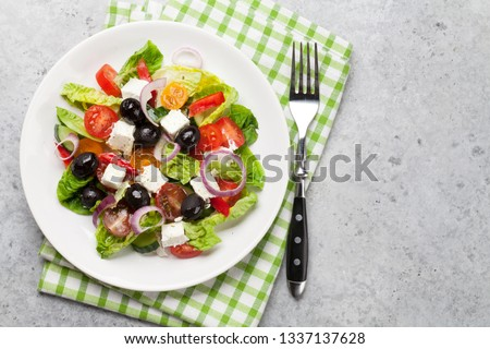 Greek salad with cucumber, tomato, pepper, lettuce, onion, feta cheese and olives, dressed with olive oil. Top view with space for your text