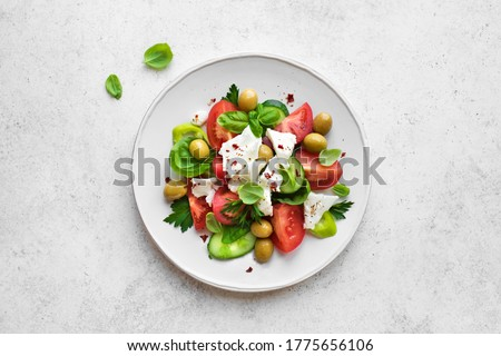 Greek Salad with Cucumeber, Olives, Feta Cheese, Tomatoes and Fresh Basil. Homemade fresh Mediterranean salad with goat cheese, healthy vegetarian meal, top view, copy space. Foto d'archivio ©