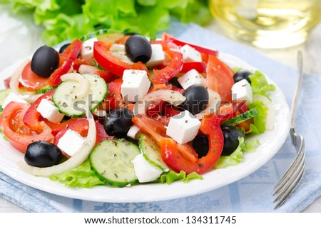 Greek salad with feta cheese, olives and vegetables on the plate closeup