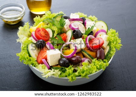 Greek salad with feta cheese, organic black olives, juicy tomatoes, red pepper, red onion, cucumber and lettuce.