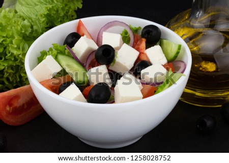 Greek salad with fresh vegetables, feta cheese and black olives on a dark background. #1258028752