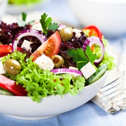 Greek salad with juicy tomatoes, feta cheese,  lettuce, green olives, cucumber, red onion and fresh parsley. Homemade food. Symbolic image. Concept for a tasty and healthy vegetarian meal. Close up.