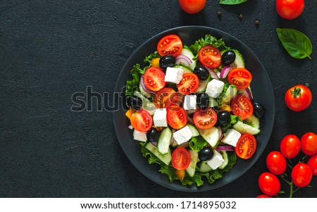 Greek salad with tomato and fresh vegetables in white bowl on dark background. Top view