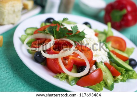 Greek salad with tomatos, mozzarella cheese, onions, olives