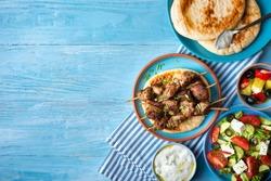 Greek souvlaki with pita bread, tzatziki sauce and salad.Copy space