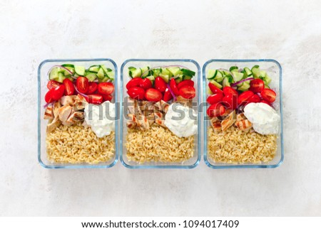 Greek style grilled chicken breasts with tzatziki and freshly diced vegetables prepared and ready to eat in a take away lunch boxes, view from above, space for a text