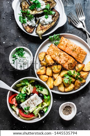 Greek style lunch table - baked lemon salmon with potatoes, greek salad, grilled eggplant with tzadziki sauce on dark background, top view. Flat lay