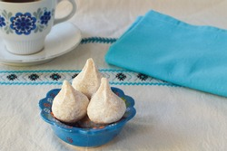 Greek traditional almond cookies, amygdalota from Cyclades in Greek blue bowl and vintage cu of coffee, on the embroidered tablecloth