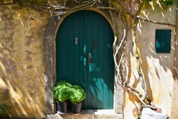 Greek traditional house facade with a  green arched wooden door on a weathered stone wall in Aroniadika village, Kythira island Attica Greece.
