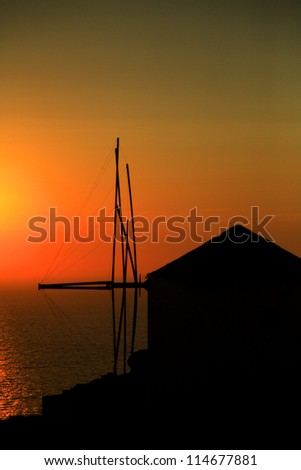 Greek windmill silhouetted against the sunset Oia Santorini