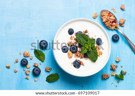 Greek yogurt granola and blueberries on blue table top view. Healthy food nutrition, snack or breakfast. #697109017