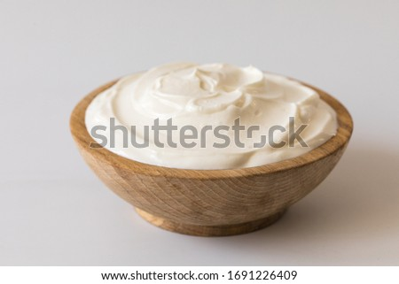 Greek yogurt in a wooden bowl. Healthy breakfast.Homemade Fatty Dairy product, sour cream, mayonnaise.