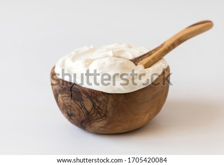 Greek yogurt in a wooden bowl. Healthy breakfast.Homemade Fatty Dairy product, sour cream, mayonnaise. ストックフォト ©