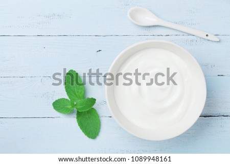 Greek yogurt in bowl decorated mint leaf on blue rustic table top view.