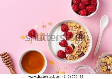 Greek yogurt in bowl with raspberries, honey and muesli on pink table top view. Healthy diet breakfast.