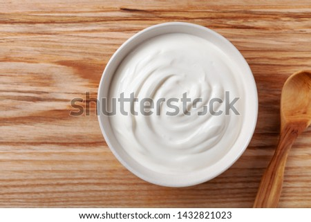 Greek yogurt in white bowl on wooden table top view.