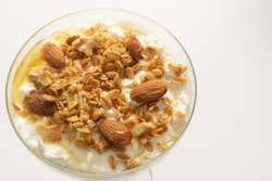 Greek yogurt served in a glass cup accompanied with granola, walnuts and honey. Traditional Greek food. Healthy and without preservatives.