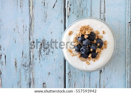 Greek yogurt with blueberries and granola, downward view on a rustic soft blue wood background #557593942