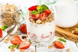 Greek yogurt with fresh strawberry and granola in glass jar. Parfait.