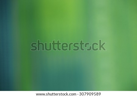 Green abstract defocused background. Green color hue picture with yellow glare. Full frame picture