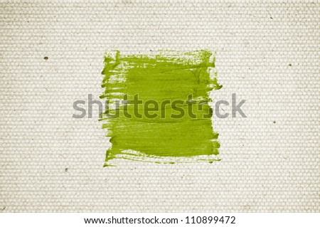Green abstract hand-painted brush stroke daub over vintage old paper