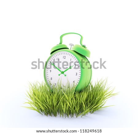 Green alarm clock in a patch of grass