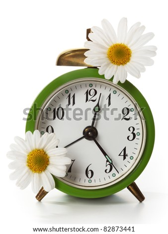 Green alarm clock with daisy flowers on white