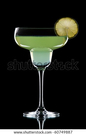 Green alcohol cocktail with green lime isolated on black