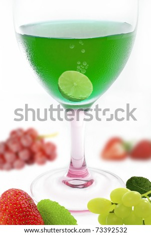 green alcohol cocktail with mix fruit on white background