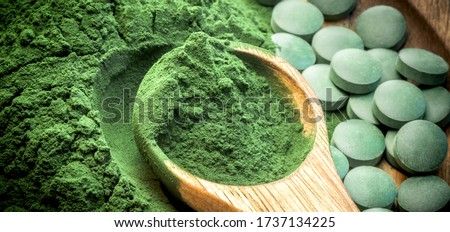 Green algae in powder and pills - chlorella, spirulina in wooden spoon on wooden background - closeup - banner design. Foto stock ©