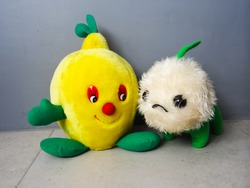 green alien and yellow fruit doll on grey background