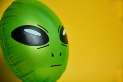 green alien looks,yellow background