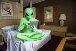 Green alien sitting using tablet computer on the bed in an old-fashioned room