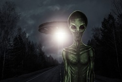 Green alien with black large glass eyes on the background of a flying saucer. UFO concept, aliens, contact with extraterrestrial civilization.
