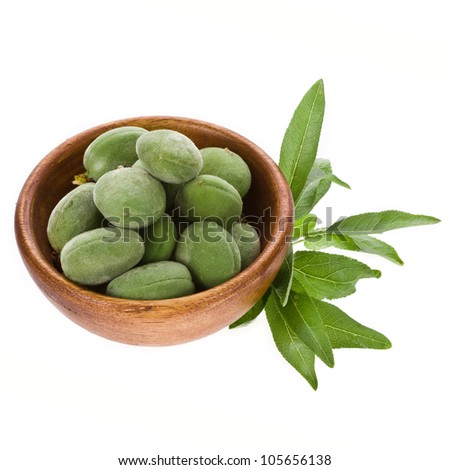 Green almonds in wooden bowl  isolated on a white background.