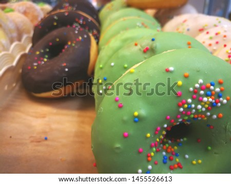 Green and black donuts sprinkled with colorful sugar