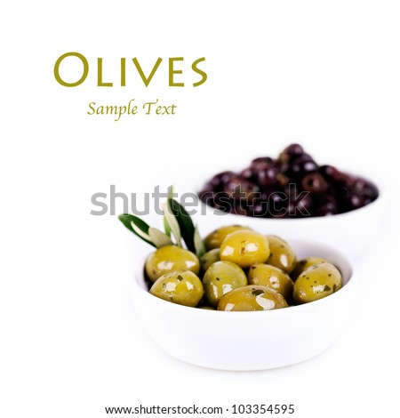Green and black olives in a white ceramic bowl with olive branch. Isolated on white with space for text.