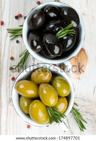 green and black olives on wooden surface