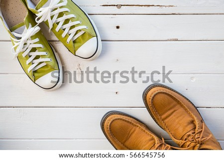 Green and brown shoes on wooden white background, top view #566545756