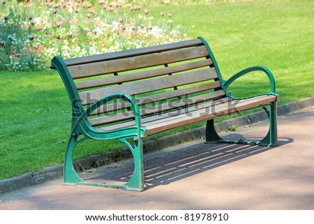 Green and brown wood bench in a park with grass and flowers behind