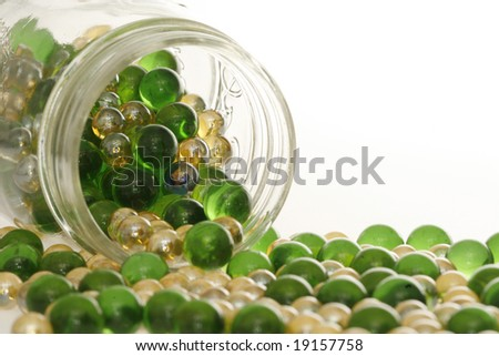 Green and Gold marbles spilling out of a jar.